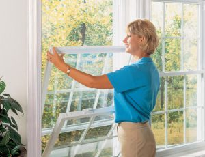 New double-hung windows being opened by homeowner